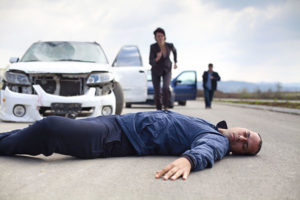 Walker injured in a car accident motionlessly lying down on the road. A person who is driving cars running to helps to injured man